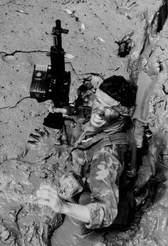 SEAL team member moves through deep mud as he makes his way ashore from a boat during a combat operation in South Vietnam May 1970. Note a MK 23 5.56mm machine gun.