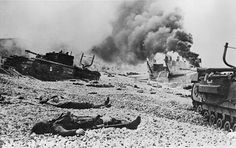 (3/12) Dead soldiers and destroyed equipment lie on the pebble beaches of Dieppe after the 19 August 1942 Dieppe Raid. Note the Y-shaped exhaust pipe extensions on the Churchill tanks, designed to allow wading.