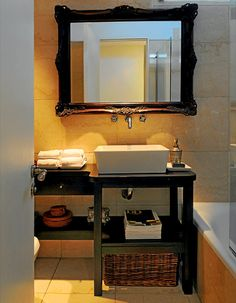 Sobrio y y elegante, con  paredes de mármol travertino y un gran  marco antiguo para el espejo. Está ubicado sobre la bacha moderna, que apoya en el mueble a medida  (Sergio Ayala).  Simplicidad y materiales  cuidadosamente seleccionados.