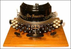 The type-bars in this 1892 Franklin Typewriter, stand up vertically, behind the curved shield and swing down to strike the top of the platen (roller) when typing. One can see what is being typed, but one needs to sit up straight to see over the shield. Old Fashioned Typewriter, Antique Typewriter, Underwood Typewriter, Writing Machine, Vintage Typewriters, Vintage Suitcases, Vintage Luggage, Phonograph, Modern