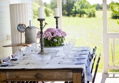 On the other end of the 12- by 50-foot back deck sits a long antique scrubbed pine table for outdoor dinner parties. Though probably American, the table takes on a French country vibe when topped with white and blue linens and vintage glassware and dishes.
