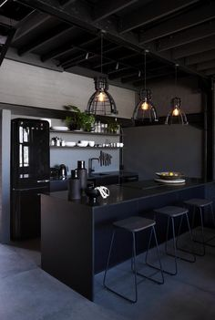 Three Factory pendant lights hang above the granite kitchen counter. White bone beads in a Peruvian vessel and lemons in a vintage Makenge basket leap out from the black.