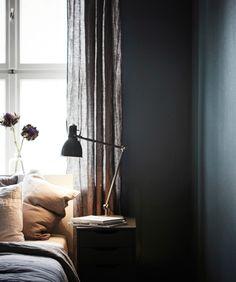 Foto eines Betts mit Ablagetisch vor einem Fenster, das von einer dunklen Wand…
