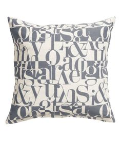Cushion cover with a jacquard-weave, cotton-blend front section, solid-color cotton canvas back, and concealed zip.