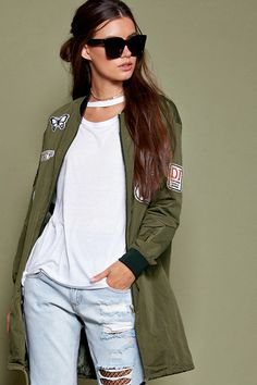 """A longline bomber jacket featuring contrast ribbed trim, zippered front, front flap pockets, drawstring hem, and various patches such as """"Route 66,"""" """"Champions,"""" """"DJ,"""" and a butterfly graphic ."""