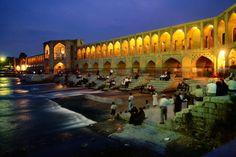 People sitting on the steps of an illuminated Khaju Bridge (Iran) at night.