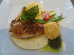 Airline herb seared chicken breast, basil tomato fondue, creamy polenta, goat cheese fritter with pesto, and parmesan crisp