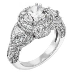 Featuring a unique combination of triangle accents combined with the appealing halo engagement ring design, the Caramia is a true stunner. At an affordable price, a total of 65 Diamond Simulants dance around the center setting, further highlighted by light millgraine detail throughout the piece. The Round Brilliant Diamond Simulant center stone at the focus of it all is held by a double-prong setting.   Center stone pictured: 1.03 carat Round cut (1.49 Round cut on hand.) Center stone…