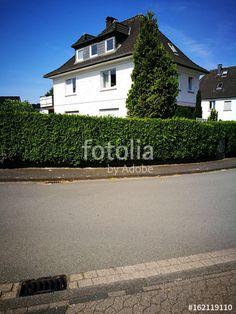 Gullydeckel an einer Straßenecke mit grüner Hecke in einem Wohngebiet in Helpup bei Oerlinghausen im Teutoburger Wald in Ostwestfalen-Lippe