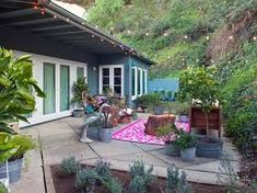 Bohemian exterior.  surrounded by nature, patterned outdoor rug, plant pots, gives off  relaxed feel.