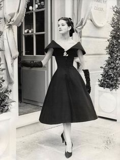 1950's Dior - black wool dress fitted bodice and bell skirt . decolletage was trimmed with a wide collar rising to point at shoulders.