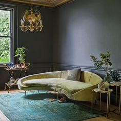 A few of my favorite things: kidney shaped sofa, brass furnishings, greenery, overdyed rug, moody gray walls
