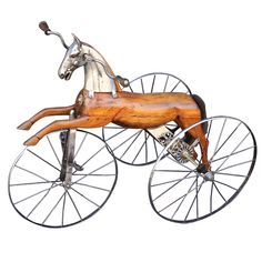French Velocipede or Child's Tricycle  France  c.1870  A 19th c. French velocipede or child's toy tricycle featuring a body of carved wood with brushed steel faceplate and glass eyes, resting on spoke wheels with brass accoutrements and horse-hair tail.    A handsome objet d'art similar to the one depicted in Claude Monet's celebrated painting of his son, Jean Monet.