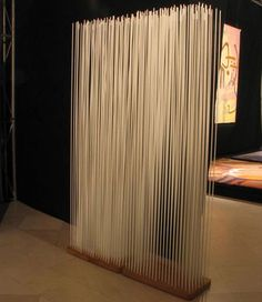 Room divider or modern art sculpture? It's difficult to tell. Fiberglass bars mounted on a plank of wood catch the light and just barely provide a glimpse of the other side.
