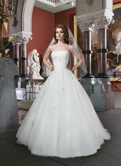 Justin Alexander wedding dresses style 8704 Ball gown features a beaded embroidered lace appliques with metallic  thread and a strapless neckline. Scattered sequin appliques are found on  the tulle skirt and chapel length train. Style features satin buttons  over the back zipper.