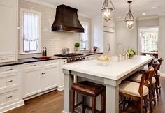 Kitchen. Kitchen remodel featuring a custom hood, Virginia Mist perimeter tops, Danby Marble island top, custom white cabinetry, and subway tile. #Kitchen Bartelt. The Remodeling Resource