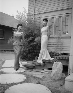 Two models in gowns designed by Kow Kaneko for a fashion show for Ladies' Night at the Nisei Veterans reunion pose for a publicity shot. They're standing in front of Kaneko's studio in Pasadena, California, 22 July 1958. The models are Etsu Andow (in the dark gown) and Masako Hirano (in the light colored gown). Photograph by Toyo Miyatake, from the Rafu Shimpo collection at the Japanese American National Museum.