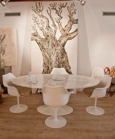Mesa tulip de mármol ovalada y sillas tulip, con la obra del artista Rebollida de fondo.Marble Tulip table with Tulip armchairs. Art by Rebollida.