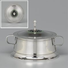 A FINE DUTCH SILVER BONBONIÈRE, CAREL J. BEGEER, AMSTERDAM, 1906, DESIGNED BY JAN EISENLOEFFEL circular, the cover centrally decorated with a green and blue geometric enamel band, angular handles, beaded borders, fully marked at the base (2) 294gr., height 14cm.