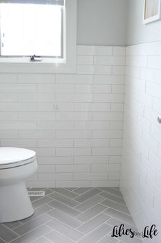 Full bathroom remodel with gray herringbone floor tile, white subway tile walls,. Full bathroom remodel with gray herringbone floor tile, white subway tile walls, black vanity and p White Subway Tile Bathroom, Bathroom Floor Tiles, Subway Tile Bathrooms, White Tiles Grey Grout, Grey Grout Bathroom, Best Bathroom Flooring, Subway Tile Showers, White Wall Tiles, Glass Showers