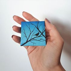 "TITLE // ""Little Bird"" SIZE // 2 inch x 2 inch, 1 cm thick MEDIUM // Professional grade acrylics on stretched canvas. It is finished with a matt varnish. This is a tiny painting I created. It features a silhouette of a little bird sitting on a branch on a blue background. It is signed"