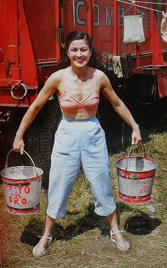 1950s Woman Circus Performer in Bathing Suit Top And Slacks Carrying Two Buckets