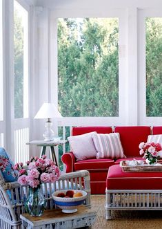 A cozy spot to enjoy morning coffee, this screened-in porch is awash in bright white. Keeping the space covered is important in the wet and humid climate. The enclosure also provides an opportunity to put architecturally interesting woodwork on display.