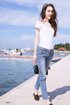 Fashion blogger Veronika Lipar of Brunette From Wall Street sharing how to look elegant in white slogan tee shirt and light blue mom jeans while by the Adriatic sea