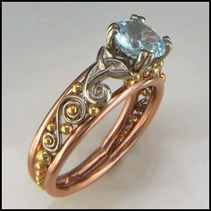 A stunning custom Celtic frame ring with 14K Rose Gold Rails, adorned with 18K Yellow Gold and 14K White Gold details set with an Aquamarine.