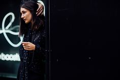 Anisa Sojka styles black sheer Nobody's Child tie-neck blouse with white star print | Loose, wide-leg trousers | Brunette straight shoulder length hair | Fashion blogger street style shot in London in front of neon lights by Moeez Ali