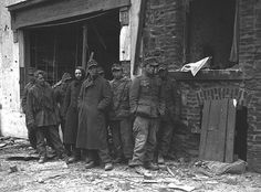 German POWs, probably from 26. Volksgrenadier-Division, stand in front of a house in ruins after they are captured by the U.S. 4th Armored Division, which helped break the siege of the city of Bastogne, Belgium. 9 January 1945.