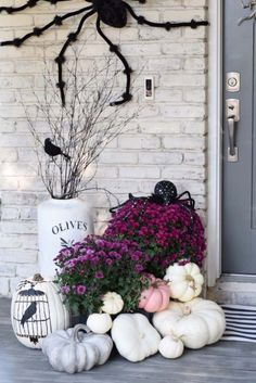 small front porch decorating ideas - pink Fall and Halloween porch decor with white and pink pumpkins paired with grey weathered gords, white over-sized vases, simple tree branches, a giant spider, and some black birds silhouettes #frontporchideas #outdoorfalldecoratingideas #smallfrontporchdecoratingideas