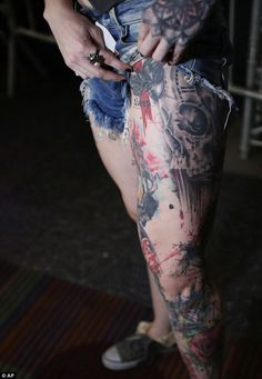 This woman hitches up her jeans to show of the design on her left leg, pictured which includes a skull