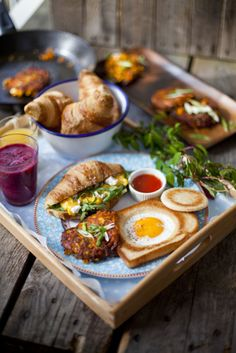 A great breakfast: eggs in basket on a wheat toast, croissant with cheese and herb medley, and hash-browns, with a berry smoothie and an orange juice shot.