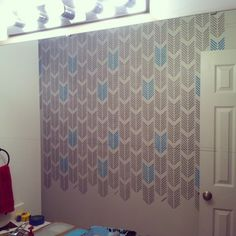 Stenciling a DIY accent wall in a bathroom using the Drifting Arrows stencil pattern. http://www.cuttingedgestencils.com/drifting-arrows-stencil-pattern-diy-decor.html