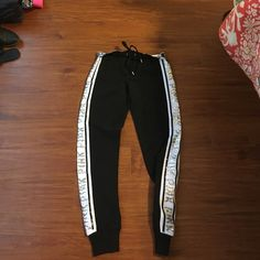 NWT VS Pink Gym Pants with Sequins NWT VS Pink Gym Pants with Sequins! Black with white stripe down the side! The white stripe has the word PINK in sequins! Still has all original tags and have not been worn! Retail for $45.95! Buy with the tank top also listed and I will bundle both for $60! (negotiable) please let me know if you want to bundle so I can make arrangements! Victoria's Secret Pants Track Pants & Joggers