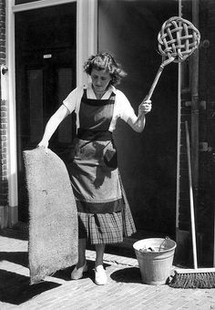 Housewife cleaning doormat with carpet-beater. The Netherlands, [1955].
