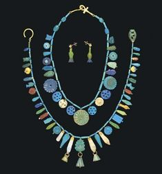 TWO EGYPTIAN FAIENCE NECKLACES  NEW KINGDOM, DYNASTY XVIII, 1550-1307 B.C.  with a modern hook closure; one with a similar assortment of amulets, also including scarabs and floral rosettes, with a modern hook-and-ankh closure; together with two cornflower amulets mounted as earrings with modern gold ear posts