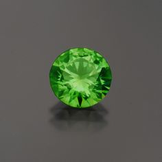 Russian demantoid garnet, above, 3.51 carats, dimensions 9.38 x 5.8 mm. Below, the same demantoid under different lighting conditions, bringing out the phenomenal dispersion from within. (Photos: Above, Mia Dixon; Below, Jason Stephenson)
