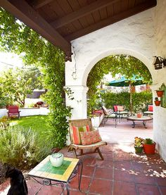 A jasmine-covered arch separates the patio from the interior courtyard, which is partly paved with colored cement to create an outdoor dining room. The light fixture is original.