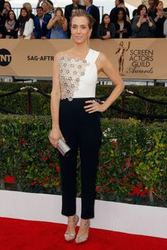 Kristen Wiig in a Roland Mouret jumpsuit with a Jimmy Choo clutch and Miu Miu shoes.