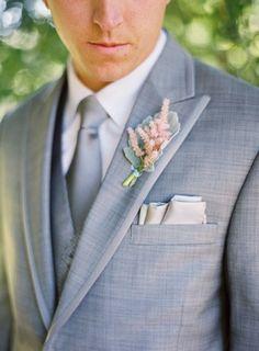traje gris claro con un chaleco y corbata, el ojal rubor