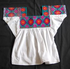 This colorful embroidered blouse comes from the town of Huitzitzilingo, Hidalgo -- a nahuatl speaking community in NE Mexico.  Many women in Huitzitzilingo still wear hand embroidered blouses on a daily basis and their blouses are embroidered in a wide variety of different patterns and colors