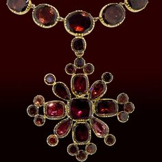 18K Yellow gold Georgian garnet necklace composed of a graduated straight line of oval garnets set in cut down collets with a detachable cross motif set with cushion, pear and round cut garnets. The garnets are a lovely orangish, brownish red with a violet cast. This is a very desirable example of Georgian jewelry as it is as wearable as it is beautiful. The detachable pendant measures 2 1/2 inches by 2 inches