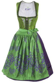 Edles Dirndl der Marke Gamsbock.  Das grüne Oberteil ist mit einer Blumenstickerei und 2-farbigen Froschrüschen in grün und lila verschönert.  Der Rock ist lilafarben, und ist über dem Saum mit 3 Borten akzentuiert.  Die grün schimmernde Schürze ist mit einer Herzwebung verziert.