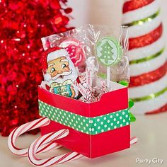 All you need to make these super-cute candy favors is a few boxes of large candy canes, red plates or construction paper to create the box, some festive ribbon to decorate it, and your fave themed candy to put inside!