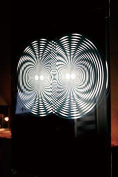 ●体験型グラフィックデザイン(卒業研究)  《コンセプト》 本作品は、グラフィックデザインという2次元要素を伝える平面の表現に、3次元要素を取り入れた。 平面を立体的に見せるため、様々な考察をした結果、モアレを手法として採用。 具体的なメッセージを伝えるため、モアレが持つ予測不可能な光と影の視覚変化を利用し、 「平衡感覚を刺激する視覚効果」を生み出すことを目的とする。  《デザインキーワード》 様々な考察の末、「不思議」・「時間」・「光」の3点をキーワードとした。 万華鏡の予測不可能な視覚変化、反射板の光の屈折による錯覚、 多面レンズの光を媒体として形を変える働きなどを参考に、平面だけでなく、 空間の奥行きも感じ取ることのできるグラフィックデザインを目指した。  《期待される効果》 ・体験している人が1番の情報量を得る。 ・第3者も作品と体験している人の光景に惹きつけられる。 ・人の動きと視覚情報が連動する。 ・人と視覚情報との共有時間が発生する。  《作品解説》 作品空間の前後には、遠近感を崩す放射状のモアレを配置。 床には、地面が揺れているような錯覚を起こす…