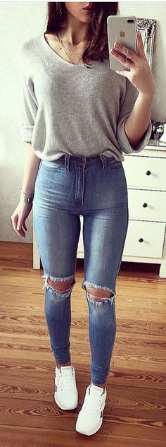#spring #outfits woman wearing gray long-sleeved top and blue jeans standing while holding iPhone. Pic by @zara__streetstyle