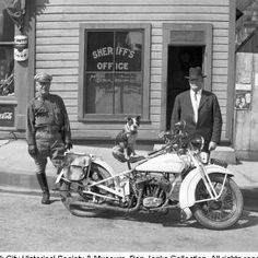 """Two men, Deputy Sam Billings and Summit County Sheriff Ephraim Adamson, stand facing camera next to white Harley-Davidson motorcycle, with dog named Dodo (who belonged to photographer's daughter, Thelma) sitting on seat looking toward camera. Sheriff's Office at 509 Main St. in background. Sign on motorcycle reads: """"SUMMIT COUNTY PATROL."""" Date:1932"""
