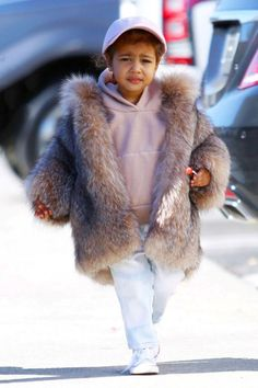 North West elevates her casual street style look of a pink sweatshirt, matching baseball cap and Chuck Taylors with a chic fur coat.